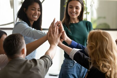 Excited cheerful multi-ethnic young employees group celebrating great common work results giving high 5 five feels motivated by business success career growth, team building concept close up arms view