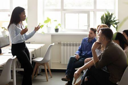 Gruppe von Praktikanten oder Unternehmensmitarbeitern, junge und ältere Fachleute, die auf Stühlen im Co-Working-Raum sitzen, dem Business-Trainer der afrikanischen Ethnizität zuhören, neue Kenntnisse im Unternehmensschulungskonzept erwerben Standard-Bild