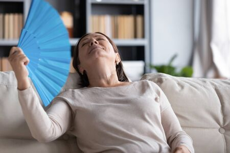 Relaxed middle-aged woman sit rest on comfortable couch in living room feel overheated wave with hand fan, senior female relax on cozy sofa feel hot breathe fresh air from waver take nap at home