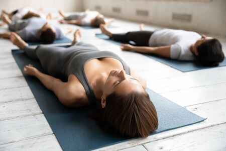 Beautiful woman practicing yoga at group lesson close up, doing Savasana exercise on mat, young sporty people relaxing in Corpse pose on floor, meditating in modern yoga studio, center