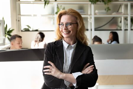 Confident middle-aged businesswoman with arms crossed on chest smiling posing in modern co-working space office, independence woman in business occupies leading position in company, firm owner concept