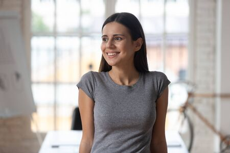 Close up of happy motivated Caucasian female employee look in distance thinking visualizing future career success, smiling thoughtful European woman worker distracted planning, business vision concept