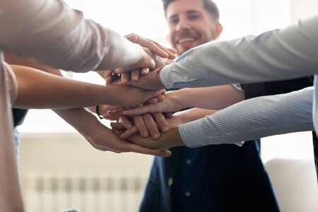 Close up view successful entrepreneurs corporate staff stacked hands together as symbol of like-minded people sharing successful project accomplishment, teambuilding activity, team spirit sign concept