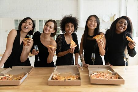 Happy multiethnic girls in black dresses look at camera smile eat pizza drinking wine have fun at hen party, overjoyed diverse ladies dressed up celebrate bridal shower or bachelorette night together 스톡 콘텐츠