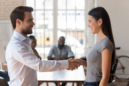 Smiling Caucasian businessman handshake excited female intern greeting with job employment, happy male boss or ceo shake hand of young woman employee get acquainted with office newcomer