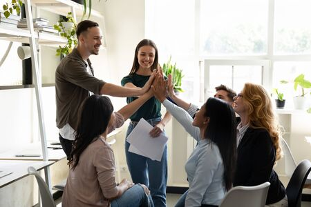 In co-working gathered diverse mates giving high 5 five feels motivated by business success, making profitable deal. Engaging in teambuilding, racial gender equality, great result celebration concept