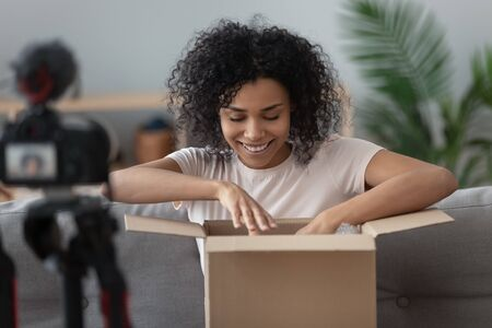 African woman sit on sofa captures on SLR or DSLR digital camera moment of unpacking ordered goods on internet to share product feedback with subscribers, vlogger filming material for channel concept
