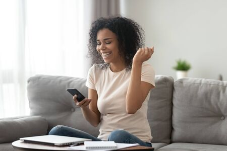 African overjoyed woman sitting on sofa holding smartphone looking at screen celebrating achievement, raise hand makes Yes I did it reach goal, got dream job, read notification lottery win sms concept Foto de archivo