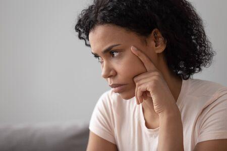 Gros plan sur le visage d'une femme mécontente pensive africaine assise sur un canapé ayant des difficultés se sent isolée, seule ou retirée, concept de réflexion sur les problèmes personnels de prise de décision, de divorce ou de rupture