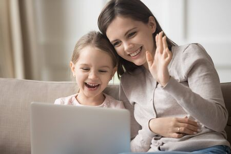 Happy mother and little daughter using laptop together, making video call, preschool adorable girl and mum watching funny video online, smiling woman waving hand, looking at computer screen