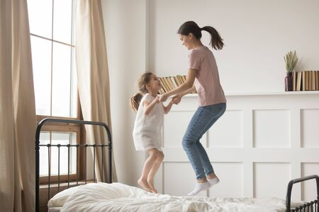 Happy young mother and cute little daughter holding hands, dancing, jumping on bed, laughing mum playing with excited adorable preschool child in bedroom, funny family activity at home, having fun Stockfoto