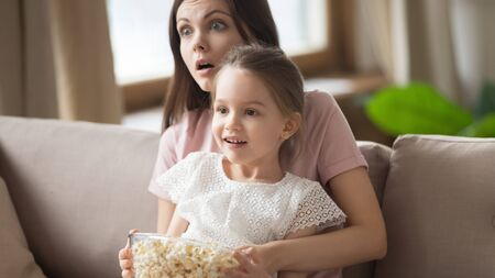 Surprised mother with little daughter watching tv, eating popcorn snack, scary or fascinating interesting movie, sitting on couch together, cute preschool girl sitting on shocked mum knees at home