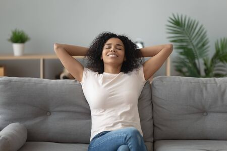 Tranquil attractive mixed-race 30s woman closed eyes fall asleep or do meditation exercise feel placidity and inner balance harmony, spend free time at home enjoy rest peace of mind and body concept