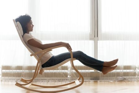 Near panoramic window african woman resting on comfortable position and angle wooden rocking chair enjoy free time lazy weekend in living room at home side profile full length view, no stress concept Banco de Imagens
