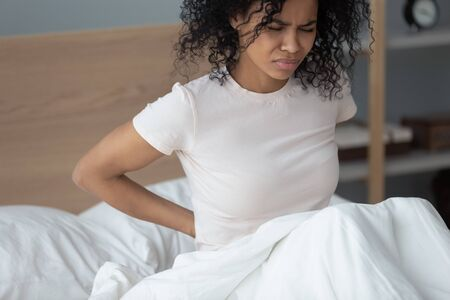 Close up african woman sit in bed wake up after night touch lower back feeling painful sensations touch rub back ease strain, incorrect sleeping position, menstrual period or spinal curvatures concept