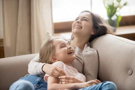 Happy mother and laughing little daughter relaxing on couch, young mum and adorable preschool child girl spending free time together at home, having fun, embracing, lying on cozy sofa close up 版權商用圖片