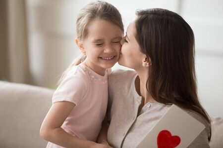 Thankful mother kissing little daughter on cheek, thanking for gift, expressing love, smiling preschool girl presenting postcard to excited mum, family celebrating birthday or women mothers day