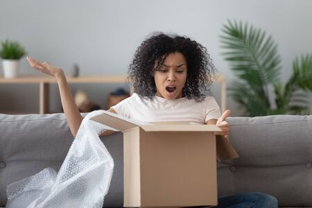 African woman unpack box feels angry received see broken ordered goods gesticulates with hands negative face expressions, concept of damaged or wrong parcel, dissatisfied client, complaints and claims