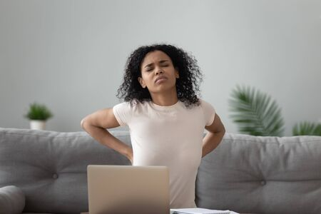 Mixed-race unhealthy african woman sitting on sofa touches lower back suffers from severe pain caused by overuse of computer lot of time working on pc, poor posture and improper spinal support concept
