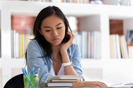 Joven estudiante asiática desinteresada se sienta en la mesa con una pila de libros distraída pensando en algo, una adolescente desmotivada se siente aburrida o perezosa soñando o visualizando, incapaz de estudiar