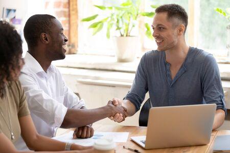 I colleghi maschi multirazziali sorridenti si siedono alla stretta di mano della riunione dell'ufficio fanno conoscenza, gli uomini multinazionali diversi eccitati si stringono la mano salutando al seminario o alla sessione di lavoro. Conoscenza concetto