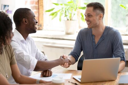 Smiling multiracial male colleagues sit at office meeting handshake get acquainted, excited diverse multinational men shake hands greeting at work seminar or session. Acquaintance concept