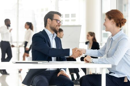 Smiling diverse businesspeople handshake greeting get acquainted at meeting in shared open office, excited man and woman business partners shake hands closing successful deal. Partnership concept