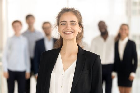 Smiling millennial female employee stand in front of diverse colleagues look at camera making picture, portrait of happy confident woman worker posing for photo, show motivation and leadership