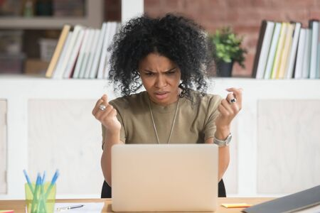 Angry african American millennial woman get annoyed using laptop having software problem, mad black female witness computer virus attack or spam, furious biracial girl experience device breakdown Zdjęcie Seryjne