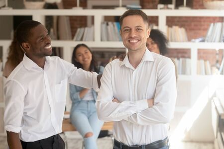 Multiracial millennial successful businessmen in white shirts stand look at camera posing in office, excited diverse multiethnic male bosses make picture together. Cooperation, partnership concept