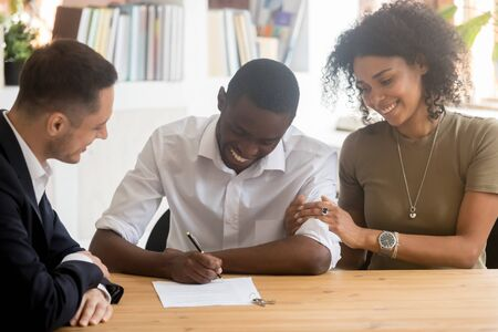 Happy black millennial couple sign contract closing deal with real estate agent buying home together, excited african American husband put signature on agreement rent take loan with wife at broker