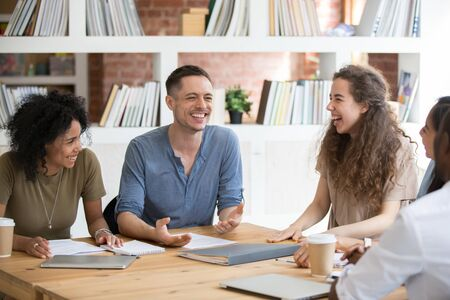 Happy multiracial millennial people sit at shared office desk laugh joking at casual team meeting, smiling diverse colleagues have fun talking chatting at work briefing. Cooperation, teamwork concept