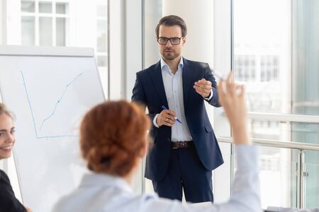 Focused male speaker or coach listen to audience question during office presentation with employees, female volunteer raise hand to ask at educational training with colleagues with company ceo or boss