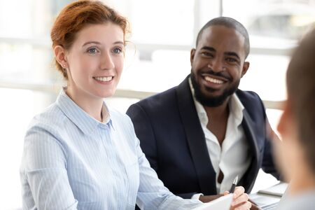 Diverse smiling employees sit at office meeting talk with colleagues discuss business project, happy multiethnic colleagues look listen to coworker talking explain share ideas at briefing