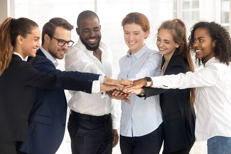 Excited multiethnic work team join stack hands motivated for shared business success, smiling diverse millennial employees engaged in teambuilding activity, show unity and support. Teamwork concept