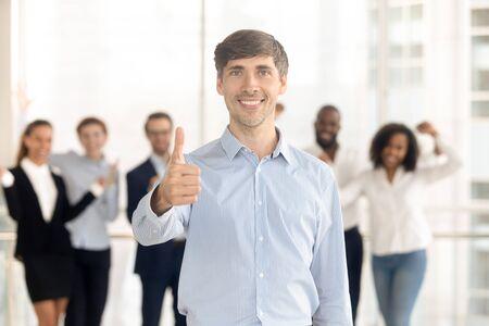 Fröhlicher kaukasischer Mitarbeiter oder Führer stehen vorne, zeigen Daumen hoch und empfehlen den Firmenservice, lächelnder männlicher Kundenblick in die Kamera gibt Empfehlung, aufgeregte Teamunterstützung motiviert im Hintergrund Standard-Bild