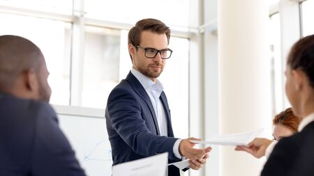 Confident millennial male speaker or presenter hold educational office training share handout presentation materials, man coach hand paperwork seminar information to employees at meeting