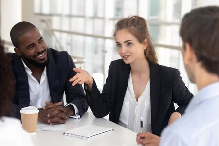 Confident millennial Caucasian female employee sit at company meeting talk explain idea or thought at briefing, woman worker speak brainstorming with business team, discuss project with colleagues Reklamní fotografie