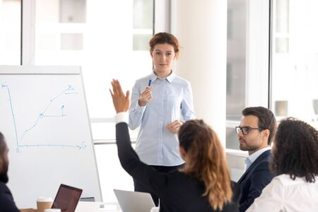 Female coach or teacher interact with diverse employees engaged in teamwork activity at office training, woman speaker ask question at seminar, motivated employee raise hand volunteer to answer Reklamní fotografie