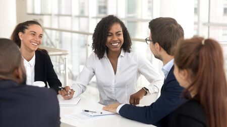 Happy multiethnic work group gather in conference room discuss share ideas talk at company meeting, smiling diverse employees speak considering startup brainstorming together at team briefing