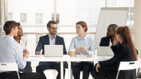 Multiethnic employees sit at office desk talk discussing business issues collaborating in boardroom, female team leader speak meeting with diverse colleagues negotiating in conference room together