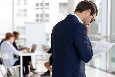 Besorgte männliche Redner stehen vor dem Konferenzraum und lesen Notizen, haben Angst, den Sitzungssaal zu betreten, ängstlich verängstigter Mann Moderator wiederholen den Papierkram-Bericht, Angst vor öffentlichen Reden