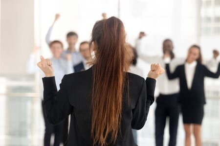 Confident successful young businesswoman make speech unify excited diverse employees, back view of millennial female team leader show power talk unite motivated colleagues. Unity, leadership concept