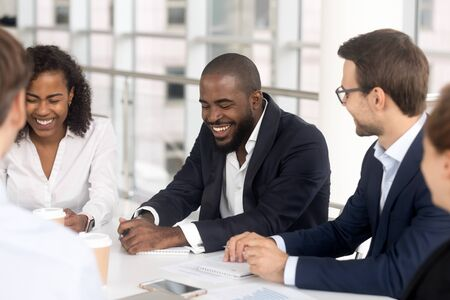 Smiling multiethnic millennial employees sit at office desk talk laugh at company boardroom meeting, happy diverse workers feel overjoyed brainstorm have fun joke at team meeting in conference room