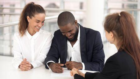 Felice marito afroamericano ha messo la firma sul contratto presso l'agenzia di brokeraggio o agente immobiliare compra casa con la moglie, eccitata coppia diversificata firma un accordo di chiusura del documento con l'agente immobiliare. Concetto di proprietà