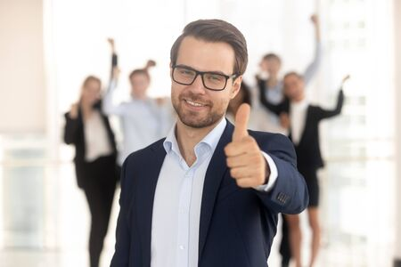 Portrait of smiling millennial businessman in glasses stand in front show thumb up recommend service or company, happy employee look at camera give recommendation, excited people at background