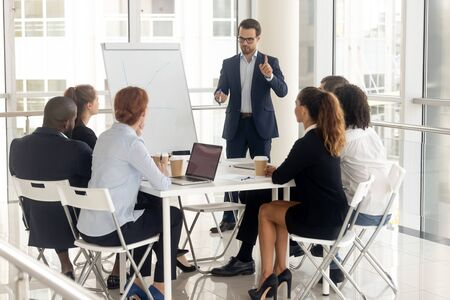 Millennial businessman in suit stand hold meeting make flip chart presentation for diverse colleagues, male coach or speaker talk present project graph on whiteboard training multiethnic work team Reklamní fotografie
