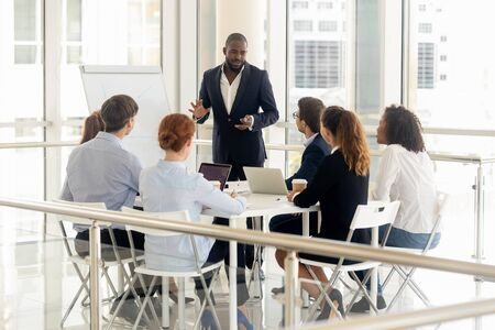 Smiling african American businessman stand make flip chart presentation for diverse work team in office, black male coach or trainer talk present strategy on whiteboard, training employees at meeting