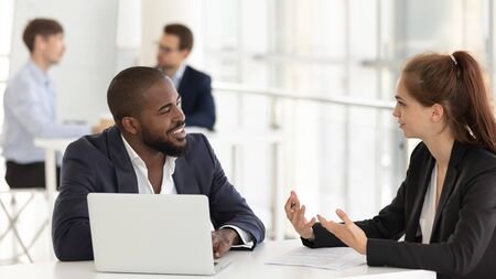 Confident millennial Caucasian female employer talk with african American male client discuss project together, focused young diverse businesspeople speak negotiating in office. Partnership concept