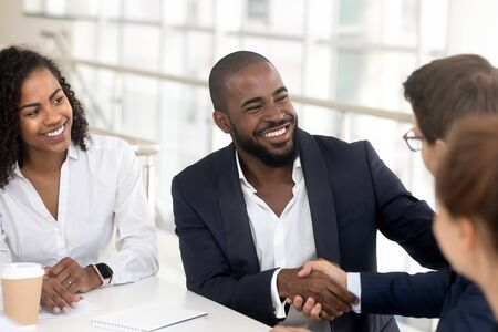 Smiling african American businessman in suit handshake male colleague get acquainted at office meeting, excited black man employee shake hand greeting with business partner a briefing Reklamní fotografie